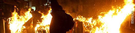 fuego en la calle con persona de negro delante
