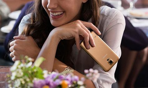 Chica con un Samsung Galaxy S5 en oro