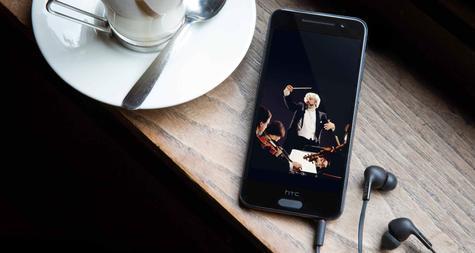 HTC One A9 con auriculares conectados y taza de café
