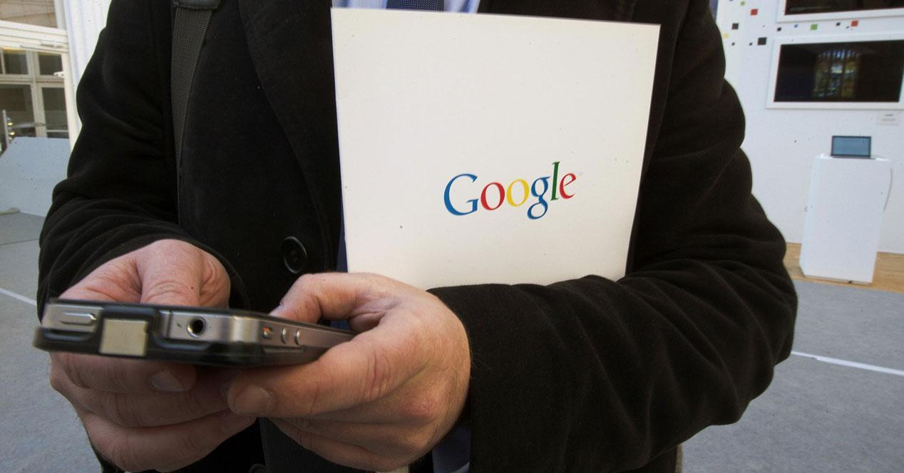 Hombre buscando en el móvil con carpeta de google