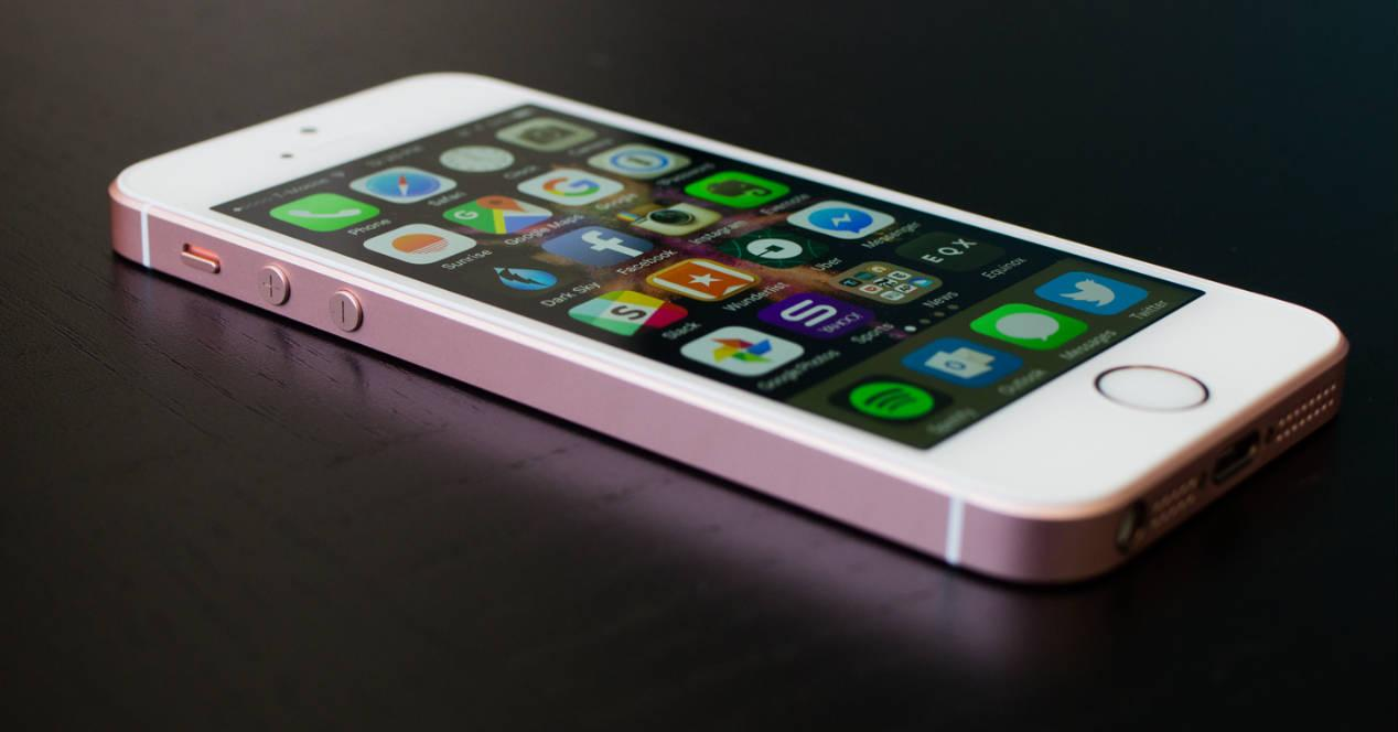 iPhone SE rosa en mesa negra