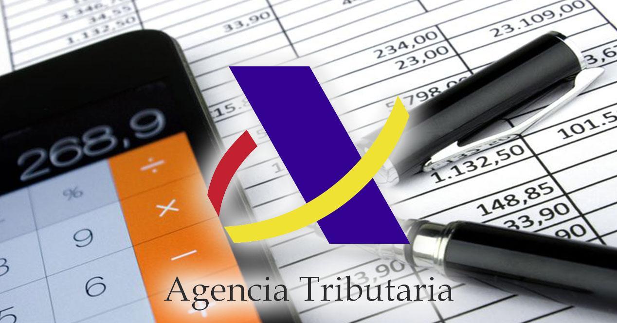 Móvil y bolígrafo con tablas y logo de la agencia tributaria