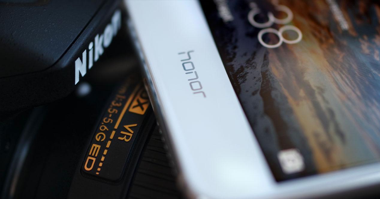 Movil Honor junto a cámara reflex