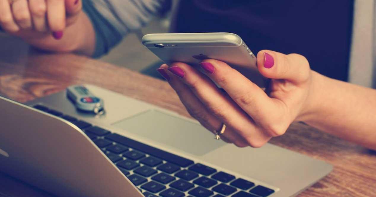 iPhone 6s en la mano junto a un macbook