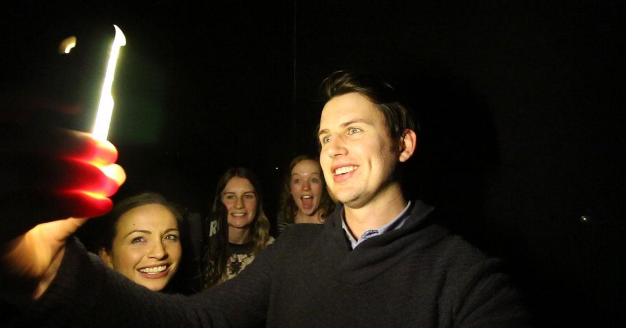 gente haciendose un selfie en la oscuridad con flash frontal para selfies